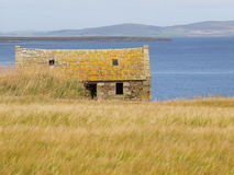 Shepherd's cottage on coastline. An old deserted shepherd's cottage on the edge of a hill.  Ocean and mountains in the background Stock Photos