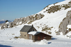 Shepherd's house on the snow slope in mountains Stock Images
