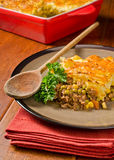 Shepherd's Pie. A freshly baked Shepherd's Pie with wooden spoon and rustic backdrop Royalty Free Stock Photography