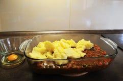 Shepherd`s pie preparation. Shepherd`s pie making. Sauce, mashed potatoes, egg and cheese royalty free stock photos