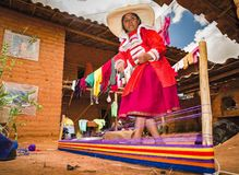 Peruvian craftswoman spinning traditional in mud house stock photography