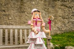 A shepherdess sat on a bench made from plant pots. A pink dress and hat. blonde pigtails or braided hair. a staff or walking stick royalty free stock photography