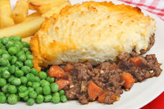 Shepherds Pie & Chips. Shepherds pie with chips and peas Royalty Free Stock Photo