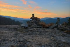 Shepherds pile on a rocky outcropping. Sunset view with shimmering clouds above a granite overlook near Muir Grove in Sequoia National Park stock photo