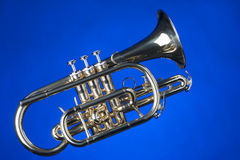 Sheppards's Crook Cornet On Blue. A gold colored brass sheppard's crook cornet isolated against a blue background in the horizontal format Stock Image