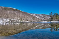 Sherando Lake Recreation Area Scenic Landscape. Sunny Winter Day after Snow with reflection of mountain in lakes while recreational hiking at campground beach stock photo