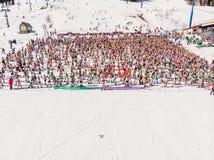 Sheregesh, regi?o de Kemerovo, R?ssia - 13 de abril de 2019: Cavaleiros do esqui e do snowboard do Fest de Grelka no biquini Foto foto de stock