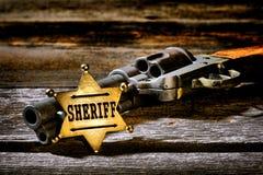 Sheriff antiguo Badge del representante de la ley y revólver occidental del arma Foto de archivo