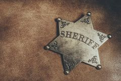 Sheriff badge on brown leather texture background. Royalty Free Stock Photo