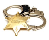 Sheriff Badge and Handcuffs. An isolated shot of a sheriff badge and pair of handcuffs Royalty Free Stock Image