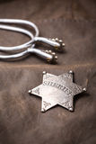 Sheriff badge and spurs. On brown background stock photo