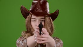 Sheriff girl holds a revolver in her hands and aiming at the villain. Green screen. Slow motion stock video footage
