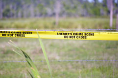 Sheriff's Crime Scene. This is a picture of a Sheriff's crime scene tape on a barbed wire fence royalty free stock image