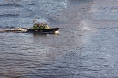 Sheriff`s cruiser cutting through the water in a blue bay stock photo