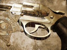Sheriff's gun. Close view to a sheriff's star and his chromed gun in which we can see the reflection of several houses of his town Royalty Free Stock Photos