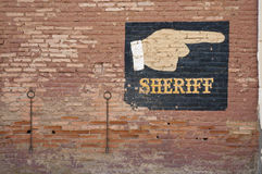 Sheriff sign. An old cowboy scene with a weathered sign painted onto the brick wall pointing the way to the sheriffs office royalty free stock image