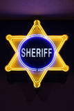 Sheriff sign. Illuminated sheriff sign on dark background close-up picture Stock Photos