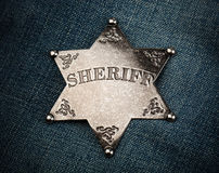 Sheriff star badge on blue denim background Royalty Free Stock Image