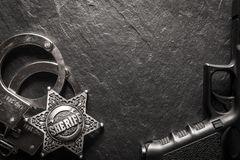 Sheriff star and handcuffs on black slate table royalty free stock photography