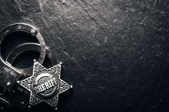 Sheriff star and handcuffs on black slate table stock images