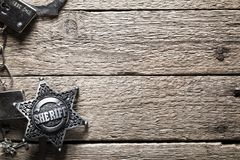 Sheriff star and handcuffs on wooden table. Closeup. Law concept background stock images