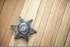 Sheriff. Star on wood table closeup stock photos