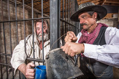 Sheriff Tends to Prisoner. Sheriff Tends to a Prisoner In a Cell stock photos