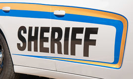 Sheriff text in black on side of a patrol car. Sheriff text in black on side of a white patrol car, lined with yellow and blue decal stripes Royalty Free Stock Photo