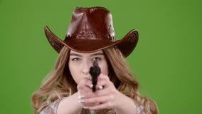 Sheriffflickan lyfter hennes huvud och tar ett skott från pistolen grön skärm långsam rörelse lager videofilmer
