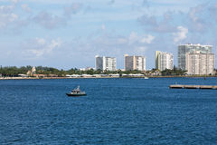 Sheriffs Boat in Bay by White Condos. Modern condos around the harbor of Port Everglades in Fort Lauderdale Florida royalty free stock image