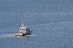 Sheriffs Boat Pulling Away in Blue Water Stock Photo
