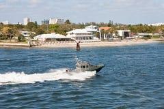 Sheriffs Boat Speeding Through Channel. A gray sheriff's boat speeding through a shipping channel stock photos