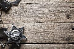 Sheriffstern und -handschellen auf Holztisch Stockbilder