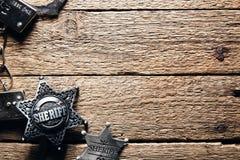 Sheriffstern und -handschellen auf Holztisch Stockfotos