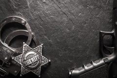 Sheriffstern und -handschellen auf schwarzer Schiefertabelle Lizenzfreie Stockfotografie