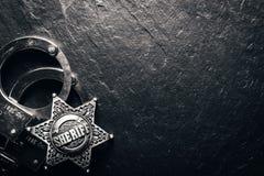 Sheriffstern und -handschellen auf schwarzer Schiefertabelle Stockbilder
