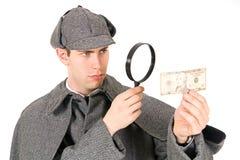 Sherlock: Agente investigativo curioso Looks a soldi con la lente d'ingrandimento Fotografie Stock