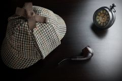 Sherlock Deerstalker Hat,  Clock And Smoking Pipe In The Dark. Sherlock Holmes Deerstalker Hat, Vintage Clock And Smoking Pipe On The Black Table Background Royalty Free Stock Photos