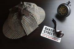 Sherlock Deerstalker Hat,  Clock And Smoking Pipe In The Dark. Sherlock Holmes Deerstalker Hat, Vintage Clock, Sign Baker Street And Smoking Pipe On The Black Stock Photo