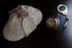 Sherlock  Deerstalker Hat,  Cuffs, Clock On The Black Wooden Tab Royalty Free Stock Image