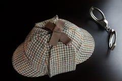 Sherlock Deerstalker Hat And Cuffs na tabela de madeira preta imagem de stock
