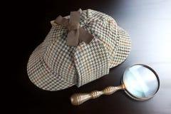 Sherlock Deerstalker Hat och tappningförstoringsglas på Bla Royaltyfri Bild