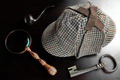 Sherlock Deerstalker Hat,  Pipe, Key And Magnifier On Black Tabl Royalty Free Stock Image