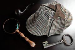 Sherlock Deerstalker Hat, rör, tangent och förstoringsapparat på svarta Tabl Royaltyfri Bild