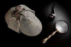 Sherlock Deerstalker Hat, rör, tangent och förstoringsapparat på svarta Tabl Arkivbilder