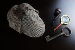 Sherlock Deerstalker Hat, rör, tangent och förstoringsapparat på svarta Tabl Royaltyfria Foton