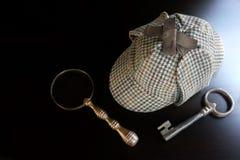 Sherlock Deerstalker Hat, tangent och förstoringsapparat på den svarta tabellen arkivfoto
