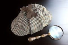Sherlock Deerstalker Hat,   And Vintage  Magnifying Glass On Bla Royalty Free Stock Image
