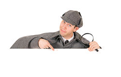 Sherlock: Detective Behind White Card Gestures Downwards. Man dressed as detective Sherlock Holmes Stock Photos