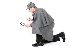 Sherlock: Detective Using Magnifying Glass To Examine Something. Man dressed as detective Sherlock Holmes Stock Photo